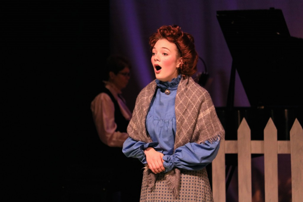 Anne singing in front of the piano, played by Cindy Piper.